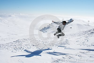 Young man jumping in the snow for fun