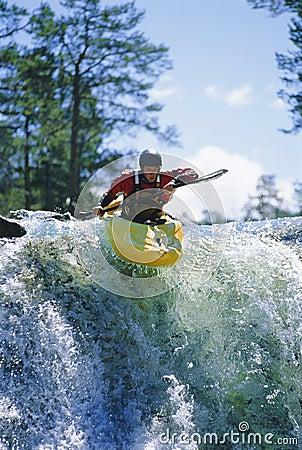 Young man kayaking on waterfall