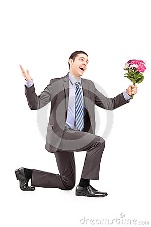 Young man kneeling and holding a bunch of flowers