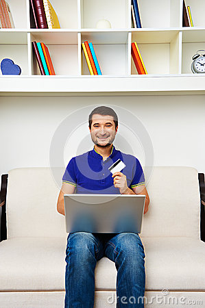 Young man with laptop and credit card at home