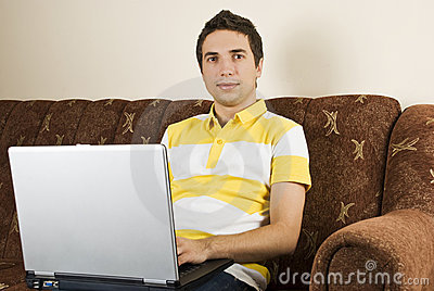 Young man with laptop home