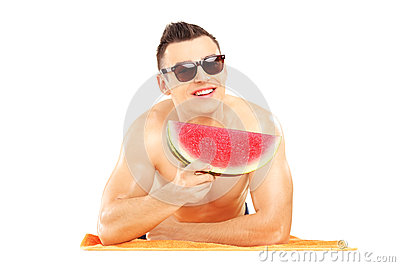 Young man laying on a beach towel and eating a slice of watermel