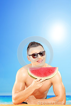 Young man laying on a towel and eating a slice of watermelon