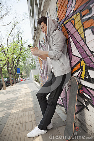 Free Young Man Leaning Again A Wall Covered In Graffiti And Texting On His Phone, Skateboard Is Next To Him Stock Photography - 33398942