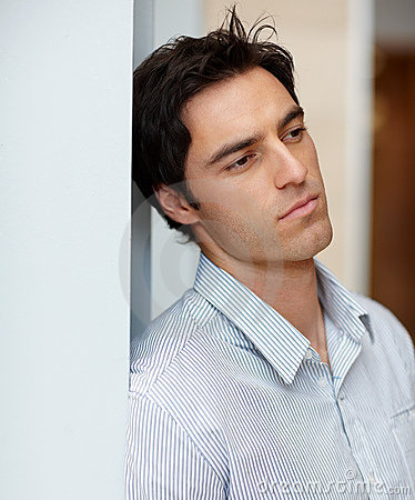 Young man leaning against a wall and thinking