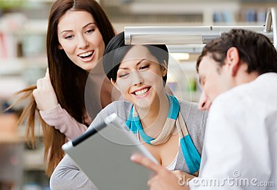 Young man at the library shows pad to two women