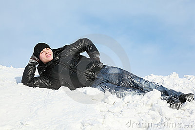 Young man lies on snow support palm