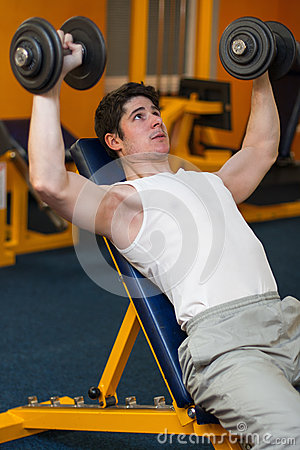 Young man lifting dumbbells in sport club