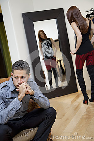 Young man looking away while thinking with girlfriend in background looking at herself in mirror