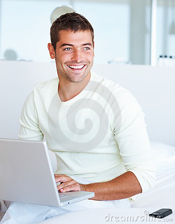A young man looking away while working on laptop