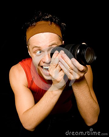Young man looks through camera lens