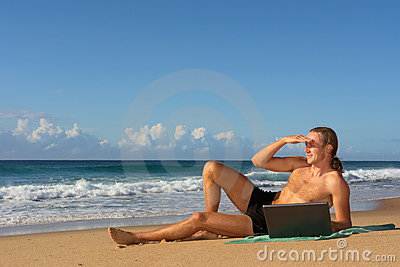 Young man looks far lying with notebook