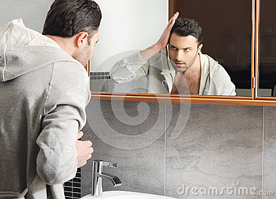 Man looks at himself in the mirror