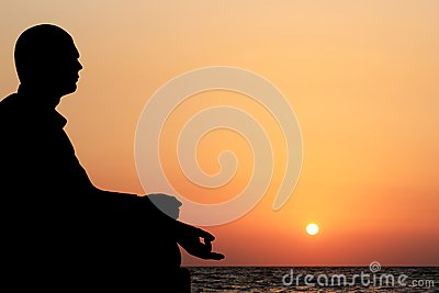 Young man in lotus position & meditating on beach
