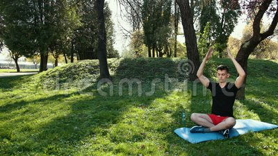 a young man in a lotus position sitting on the green grass