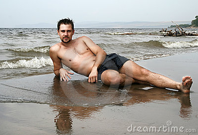 Young man lying on lonely beach