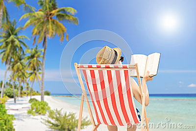 Young man lying on an outdoor chair and reading book, on a beach