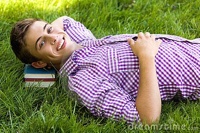 Young man lying on a pile of books