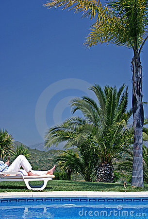 Young man lying on a sunbed holding a glass of Champagne