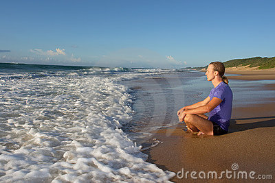 Young man meditates on beach in lotus pose