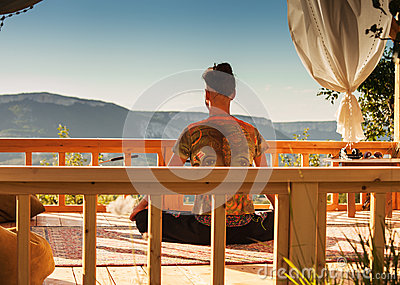Young man meditation in summer house
