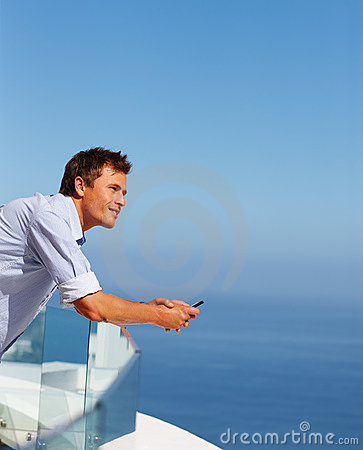Young man with a mobile on his balcony railing