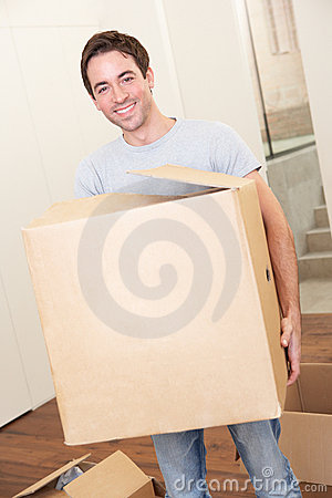 Young man on moving day carrying cardboard box