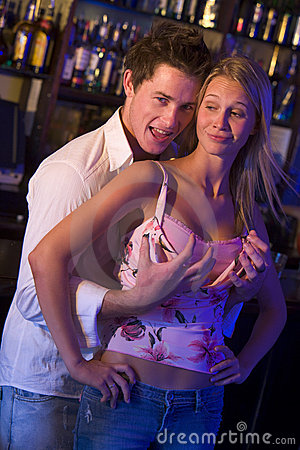 Young man in a nightclub grabbing breasts