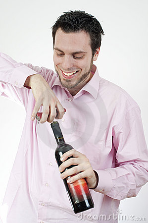 Young man Opening a bottle of wine