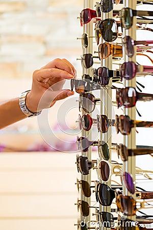 Young man at optician shopping sunglasses