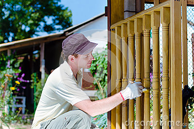 Young man painting wooden fence