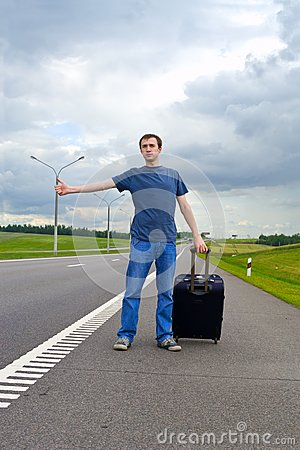 The young man pending on road with suitcase