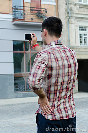 Young man photographing a building