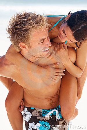 Young man piggybacking his girlfriend at the beach
