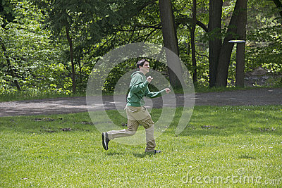 Young Man Playing Frisbee At The Park