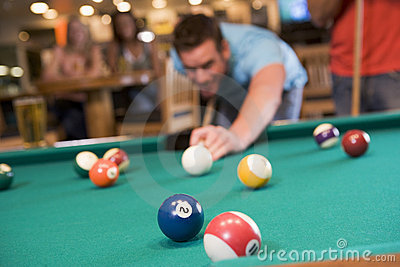 Young man playing pool in a bar