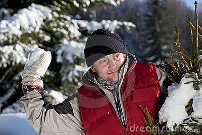 Young man playing with snowball