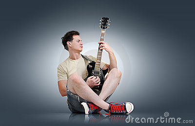 Young man plays the electric guitar