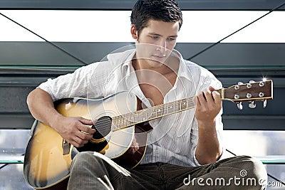 Young man plays guitar