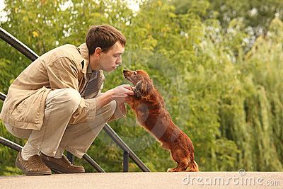 Young man plays with his adorable dachshund