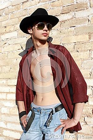 Young man posing next to a brick wall