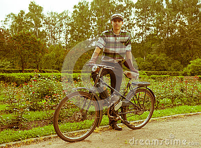 Young man posing with retro motorbike in the park.