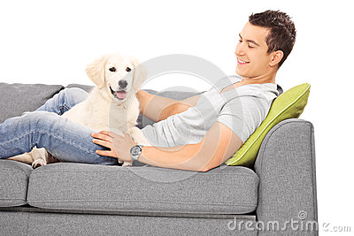 Young man and a puppy lying on couch