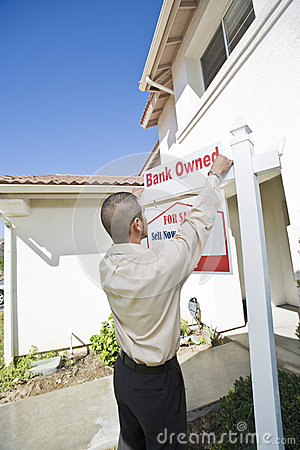 Young Man Putting Up  For Sale Notice