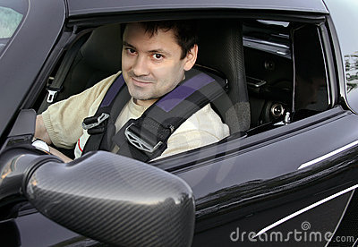 Young man, racer sitting in sport car