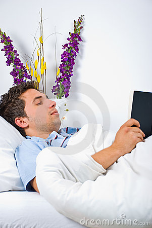 Young man reading book on bed