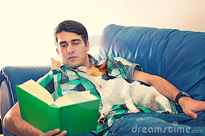 Young man reading a book with his dog on a couch