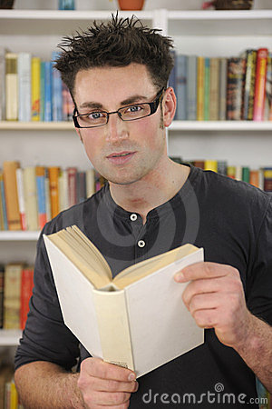 Young man reading a book in library