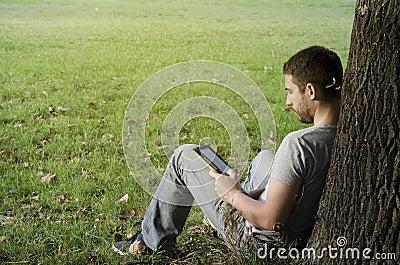 Young man reading e-book