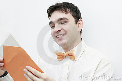 young man reading a letter smiling
